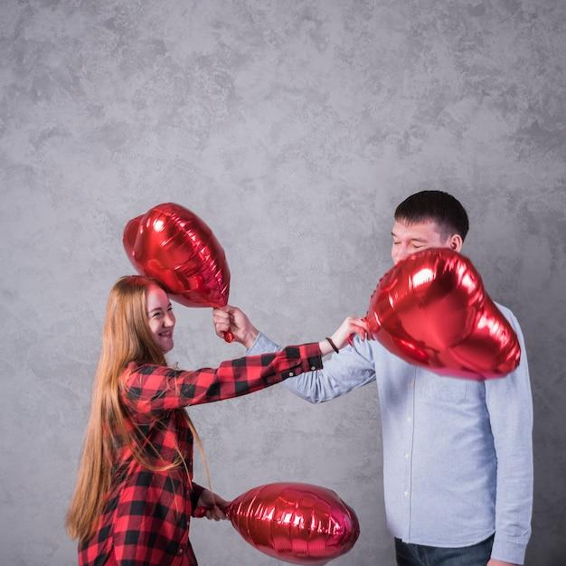 Par, tocando, com, balões coração Foto gratuita