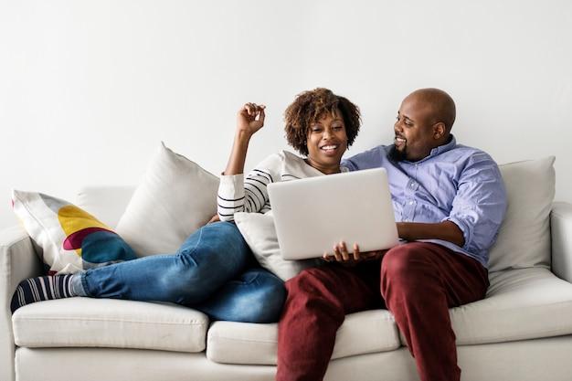 Par, usando computador portátil, junto, ligado, a, sofá Foto Premium