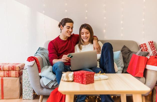 Par, usando computador portátil, ligado, sofá Foto gratuita