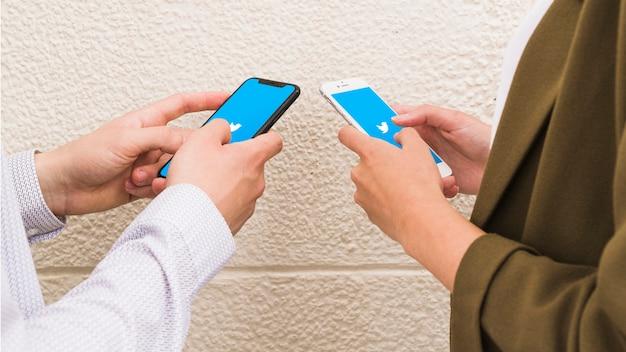 Par, usando, twitter, aplicação, ligado, telefone móvel Foto gratuita