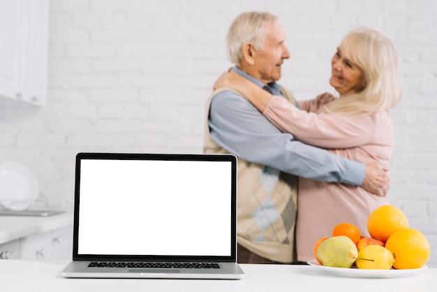 Par velho, dançar, atrás de, laptop, em, cozinha Foto gratuita