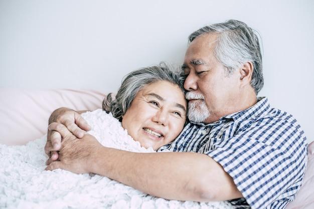 Par velho, mentindo cama, junto Foto gratuita