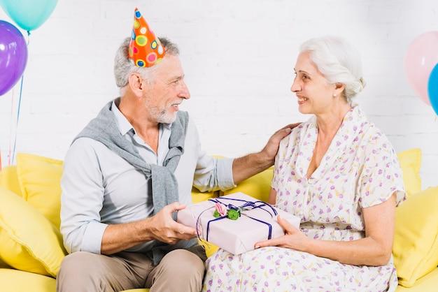 Par velho, sentar sofá, com, presente aniversário Foto gratuita