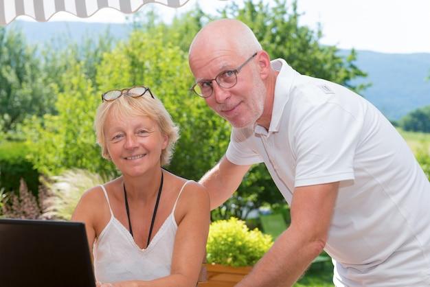 Par velho, usando computador laptop, casa Foto Premium