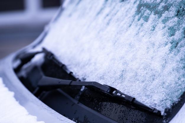Para-brisa congelado do carro coberto com o gelo e a neve em um dia de inverno. Foto Premium