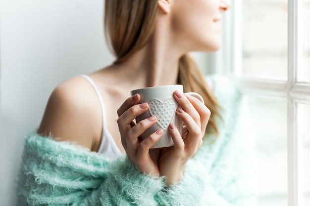 Para se aquecer na manhã fria. retrato de uma jovem mulher pela janela Foto Premium