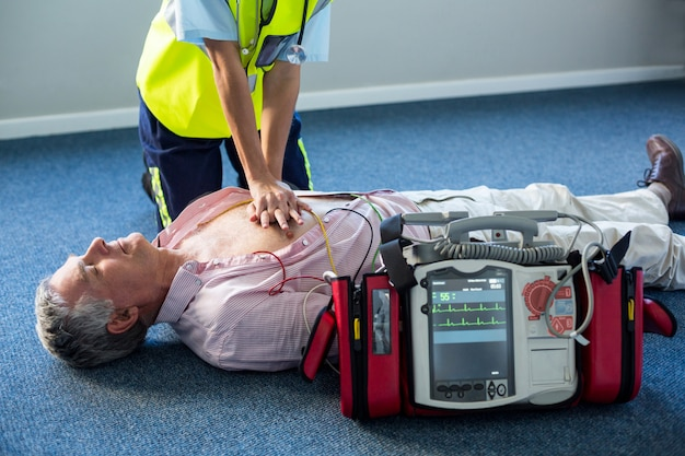 Paramédico usando desfibrilador externo durante ressuscitação cardiopulmonar Foto Premium