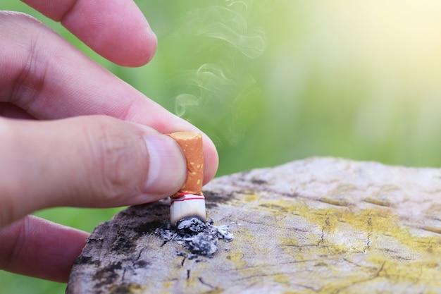 Parar de fumar parar de fumar conceito, mão caiu cigarro desceu para a mesa de madeira para parar de fumar. Foto Premium