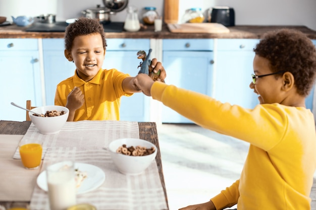 Parceiros de jogo. meninos simpáticos sentados à mesa da cozinha e brigando de brincadeira com dinossauros de brinquedo durante o café da manhã Foto Premium