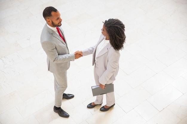 Parceiros de negócios, cumprimentando uns aos outros no corredor do escritório Foto gratuita