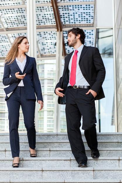 Parceiros de negócios, discutindo juntos em algumas escadas ao ar livre Foto Premium