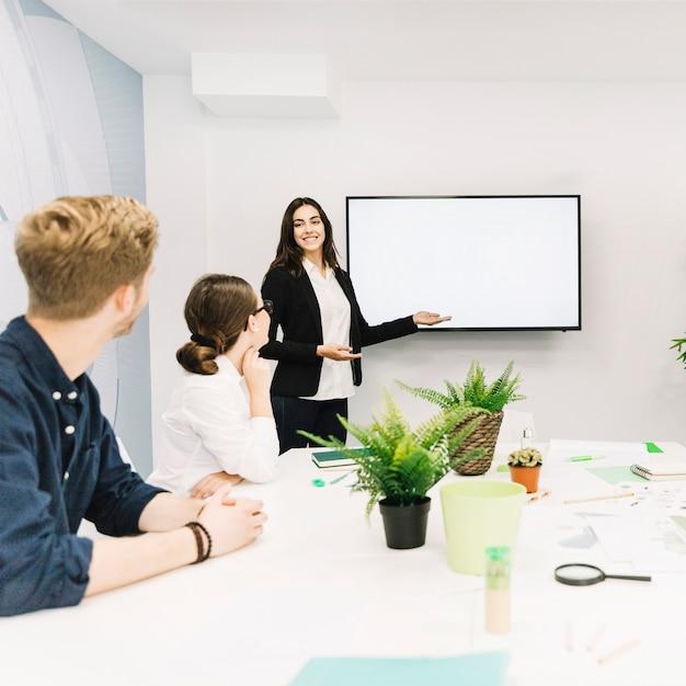 Parceiros de negócios, olhando para o gerente feminino dando apresentação Foto gratuita
