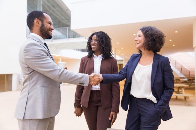 Parceiros de negócios positivos felizes terminando a reunião Foto gratuita