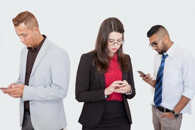 Parceiros sérios usando smartphones na reunião Foto gratuita