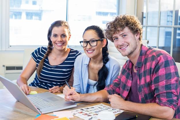 Parceiros sorridentes trabalhando em conjunto com fotografias Foto Premium