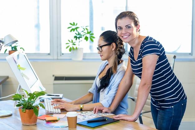 Parceiros sorridentes trabalhando juntos no computador Foto Premium