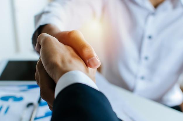 Parceria. dois empresários apertando a mão depois da entrevista de emprego de negócios na sala de reuniões no escritório Foto Premium