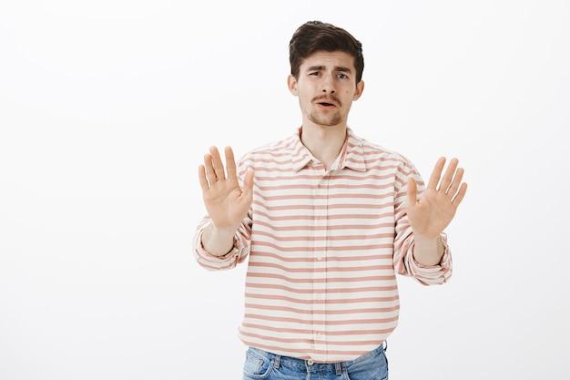 Pare de me oferecer essa porcaria. retrato de um homem europeu maduro incomodado com barba e bigode, puxando as palmas das mãos em direção a, mostrando nenhum gesto ou gesto suficiente, sugestão declinante Foto gratuita