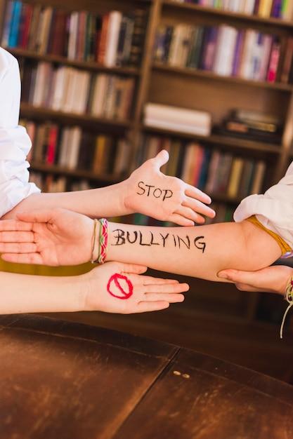Pare o slogan do bullying nos braços das crianças Foto gratuita