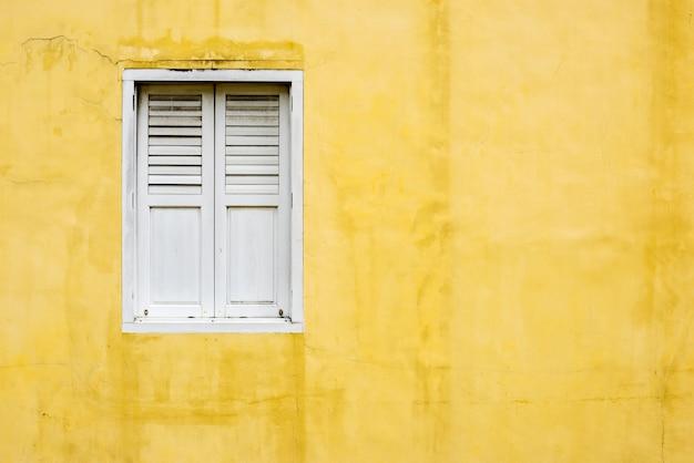 Parede amarela e uma janela branca Foto gratuita