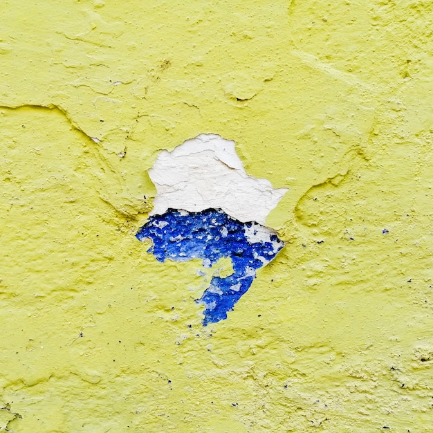 Parede amarela quebrada com azul Foto gratuita