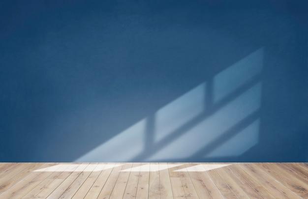 Parede azul em uma sala vazia com piso de madeira Foto gratuita
