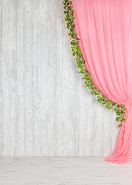 Parede cinzenta de madeira com uma cortina cor-de-rosa e flores. Foto Premium