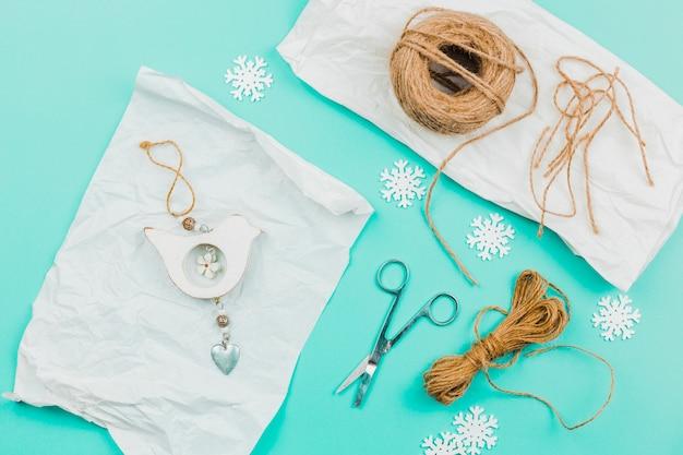 Parede de parede artesanal criativa pendurado em papel pergaminho com floco de neve; tesoura e fio de juta no pano de fundo turquesa Foto gratuita