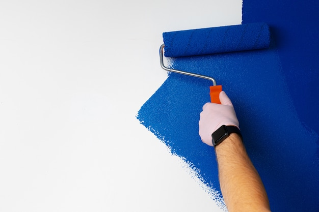 Parede de pintura de mão masculina com luvas na cor azul clássica Foto Premium