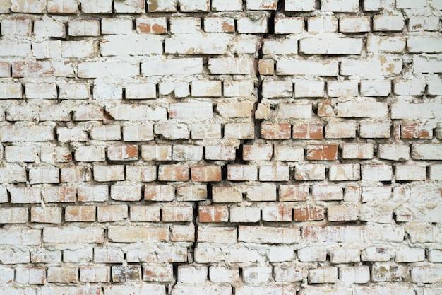 Parede de tijolos com uma grande fenda no meio. parede feita de tijolo vermelho e pintada com tinta branca rachada verticalmente fundo Foto Premium