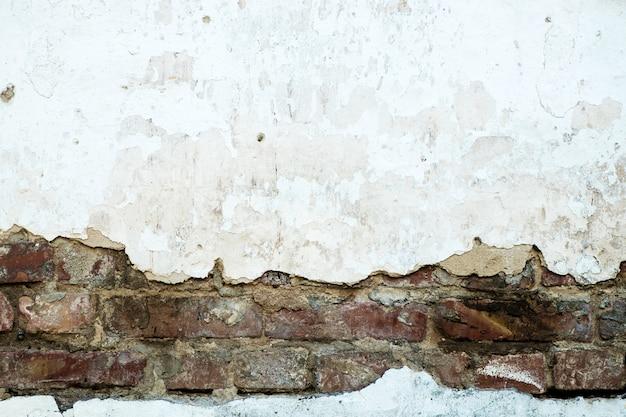 Parede de tijolos danificados, gesso rachado, plano de fundo texturizado Foto Premium
