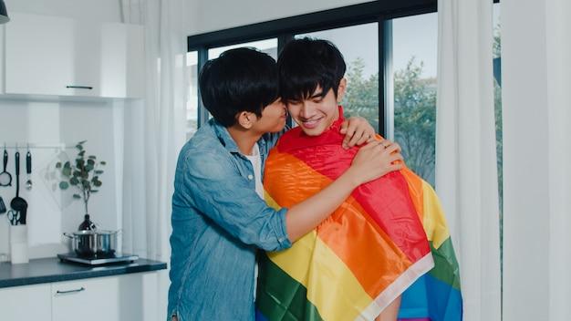 Pares alegres asiáticos que estão e que abraçam a sala em casa. jovens bonitos lgbtq + homens beijando feliz relaxar resto juntos passam tempo romântico na cozinha moderna com bandeira de arco-íris em casa de manhã. Foto gratuita