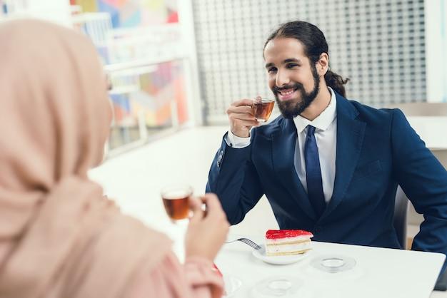 Pares árabes que sentam-se no café após a compra. Foto Premium