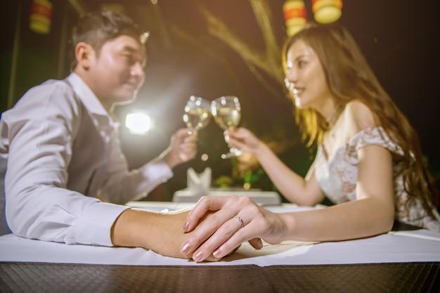 Pares asiáticos que mantêm as mãos unidas e vidros cheering do vinho. concentre-se na mão e toque. Foto Premium