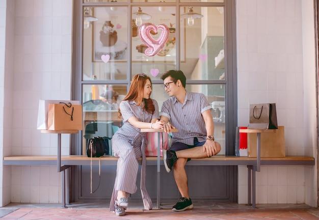 Pares asiáticos que sentam-se e que falam felizmente após a compra. Foto Premium