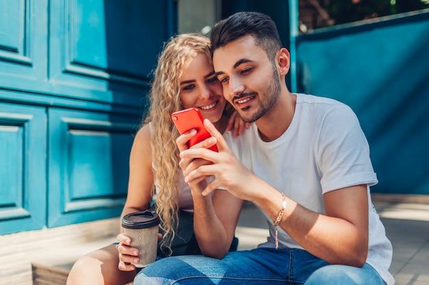 Pares da raça misturada no amor que anda na cidade. homem árabe e mulher bebendo café e usando smartphone Foto Premium