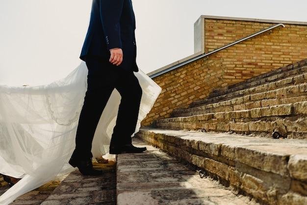 Pares do recém-casado, noiva e noivo que andam na praia. Foto Premium