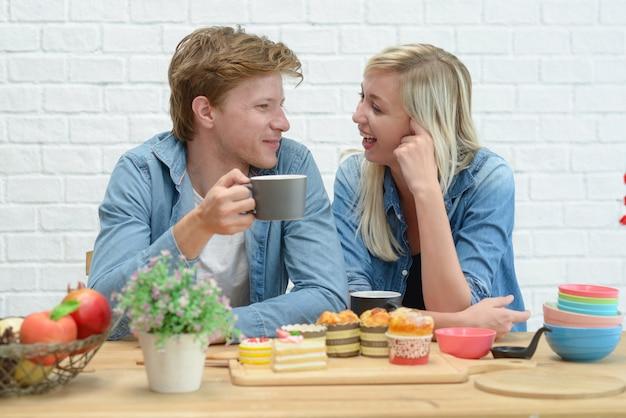 Pares felizes que comem a ruptura e a sobremesa de café na cozinha branca. Foto Premium