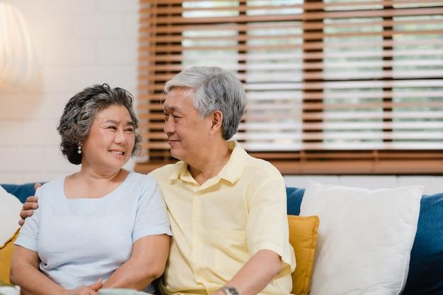 Pares idosos asiáticos que guardam suas mãos ao tomar junto na sala de visitas, par que sente a parte feliz e apoie-se que encontra-se no sofá em casa. Foto gratuita