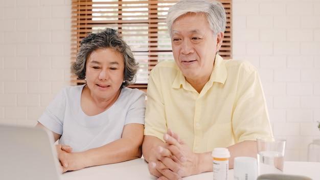 Pares idosos asiáticos que usam a conferência do portátil com o doutor sobre a informação da medicina na sala de visitas, par usando o tempo junto ao encontrar-se no sofá em casa. Foto gratuita