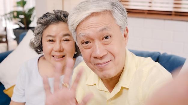 Pares idosos asiáticos que usam a videoconferência do smartphone com neto ao encontrar-se no sofá na sala de visitas em casa. Foto gratuita