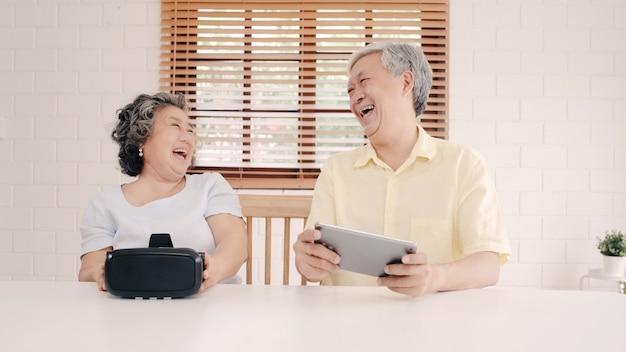 Pares idosos asiáticos usando o simulador da tabuleta e da realidade virtual que joga jogos na sala de visitas, par que sente feliz usando o tempo que encontra-se junto na tabela em casa. Foto gratuita