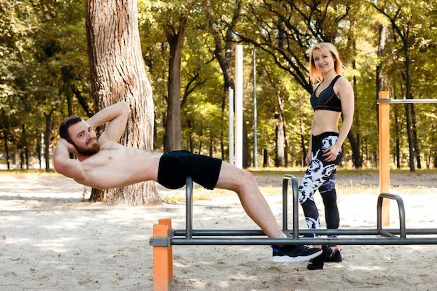 Pares novos desportivos que bombeiam os músculos abdominais em um parque no dia do outono. Foto Premium