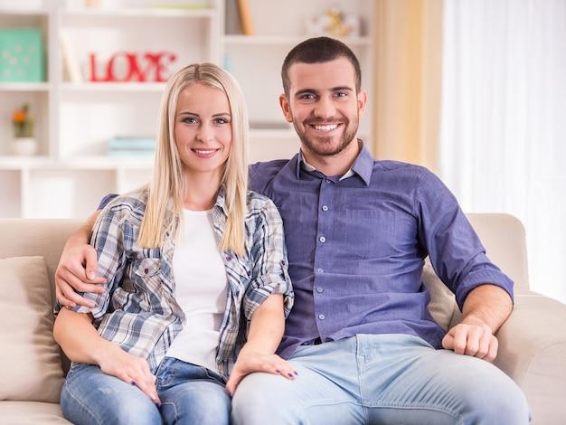 Pares novos loving que sentam-se no sofá em casa. Foto Premium