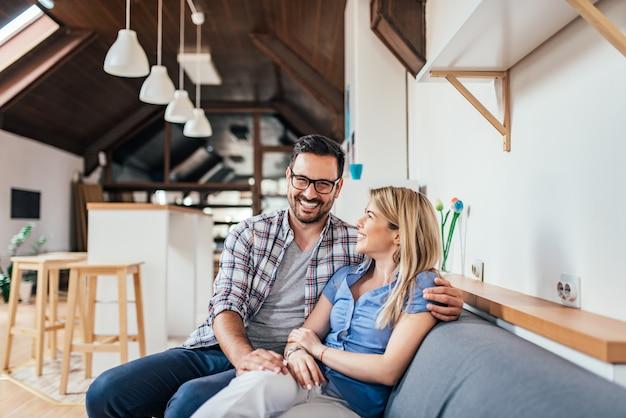 Pares novos loving que sentam-se no sofá no apartamento moderno. Foto Premium