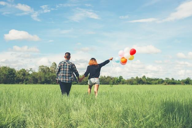 Pares que andam com balões coloridos Foto gratuita