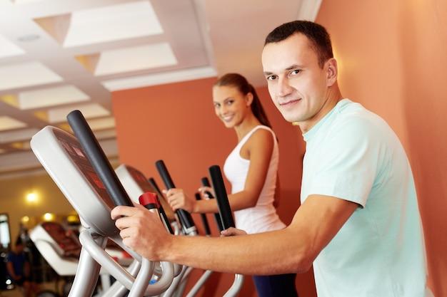 Pares que fazem exercícios jovens com aparelho elíptico Foto gratuita