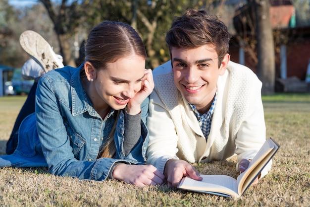 Pares que lêem um livro ao ar livre Foto gratuita