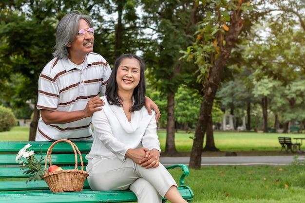Pares sênior asiáticos com felicidade do estilo de vida da cesta de fruta no parque. Foto Premium