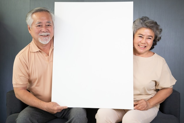 Pares sênior asiáticos que sentam-se no sofá e que mantêm o cartaz em branco branco unidos. Foto Premium